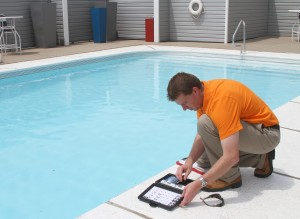 A man using equipment to test the water in a swimming pool