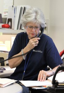 A woman reviewing documents while speaking on the phone